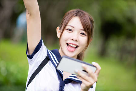 Asian high school student use mobile to play game happily on campus