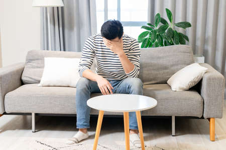 Asian man feel depressed and sitting on sofa at home
