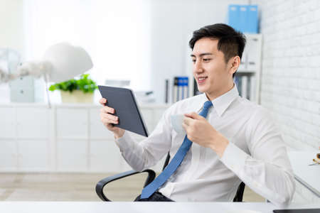 asian young businessman is reading news by tablet pc and drinking coffe in the office Stock Photo