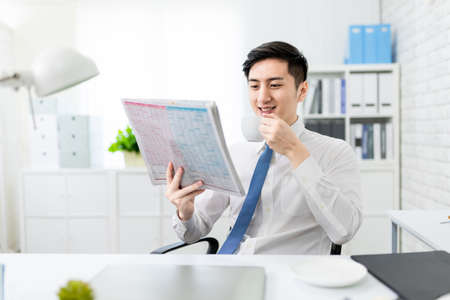 asian young businessman is reading newspaper and drinking coffe in the office