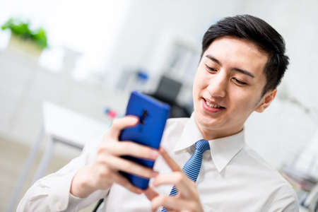 asian young businessman is using smartphone in the office Stock Photo