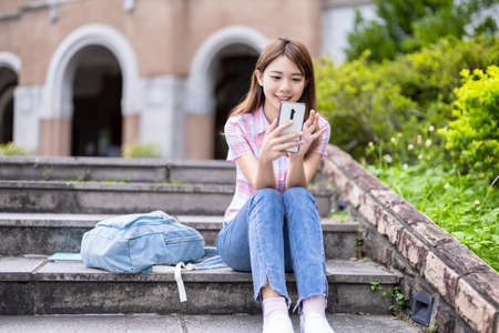 Asian college student use mobile smartphone happily on campus Stock Photo