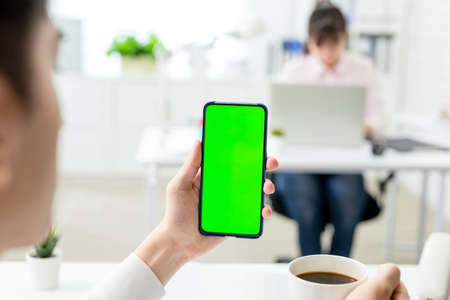 asian young businessman look to green screen smart phone in the office Stock Photo