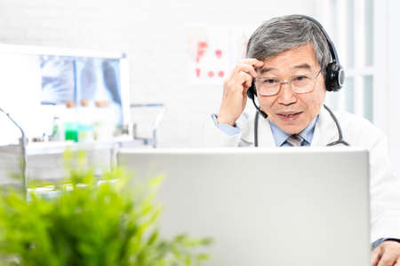 Telemedicine concept-asian senior male doctor talking headache symptom to patient on the internet and make a discussion in clinic Stock Photo