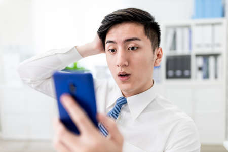 asian young businessman look on smart phone and he is shocked by unexpected social media fake news