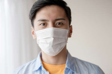 asian young man with face mask stay isolation at home for self quarantine due to an epidemic of COVID-19