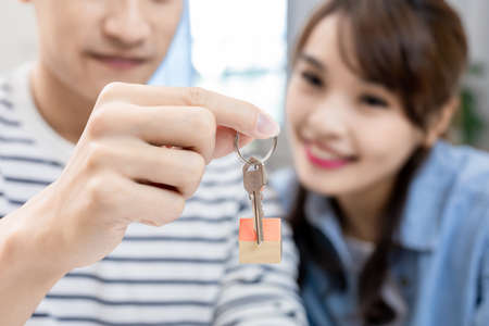 Young asian couple buying house and holding new key in hand happily Stock Photo
