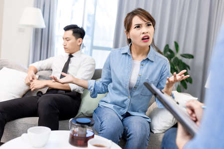 Young unhappy asian couple having marriage counseling and the wife is complaining