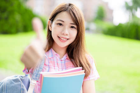 Asian college student smile to you and thumbs up on campus Stock Photo