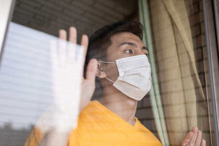 asian young man with face mask stay isolation at home for self quarantine due to an epidemic of COVID-19 and he looks out by windows