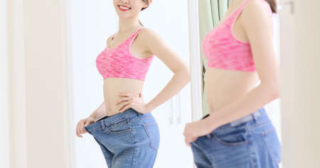 asian sport woman wear old loose jeans and look in the miror
