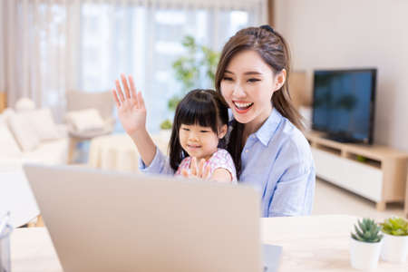 asian young woman and her daughter have video chat by laptop happily