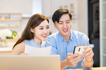 asian couple looking some information on the internet together by digital tablet at home happily