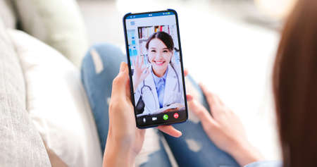Telemedicine concept-back view of asian woman has video chat with female doctor and she make a discussion with ok gesture