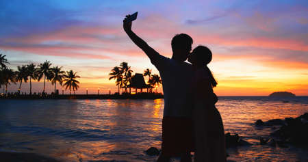 silhouette of asian couple holding each other hands and standing on the beach during sunset Foto de archivo