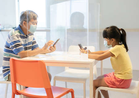 Asian old man is sitting in restaurant using smartphone with table shield to protect infection from coronavirus covid-19 Stock Photo