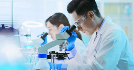 asian biological technology scientist team watch something on petri dish in the laboratory