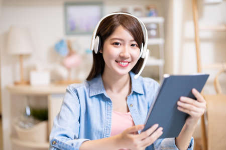 telework concept-Asian business woman is happy about her success order by raise fist gesture while she useing laptop computer to join video meeting with headset and digital tablet at home