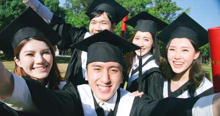 happy graduate friends take selfie in campus