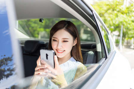 asian successful business woman use smart phone in the car