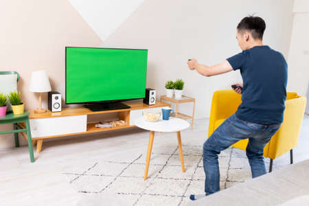 asian young man is playing and winning motion sensing game on a green chroma key TV screen and shake his arm at home