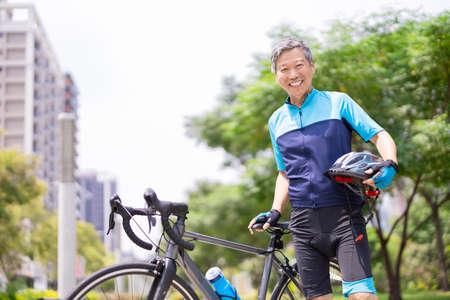 Asian old man wearing helmet and face mask is riding a bicycle in the park-enjoying sport or hobby living healthy