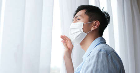 asian young man wearing face mask stay isolation at home for self quarantine due to epidemic of COVID19-he looks out the window
