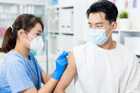 close up of asian doctor giving patient vaccination and injection in hospital
