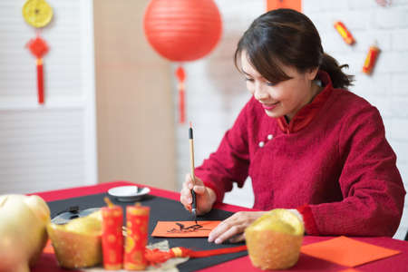 asian female writing spring festival couplets is celebrating Chinese holidays with word meaning new year and may wealth come generously to you
