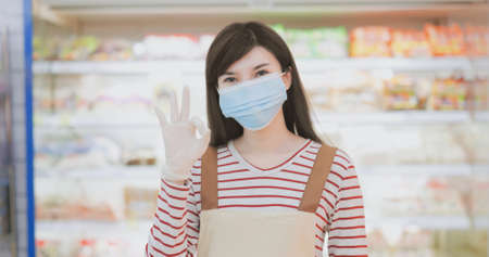smiling asian clerk is wearing face mask with gloves at grocery store during virus epidemic outbreak then shows ok gesture-look to you Banco de Imagens