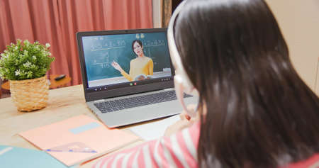 rear view of asian girl is learning math and looking elementary school female teacher teaching online through laptop at home