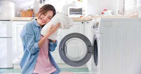 Asian housewife wash clothes happily at home