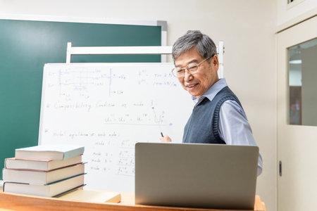 Asian mature male professor teach Engineering online through laptop in classroom at graduate school
