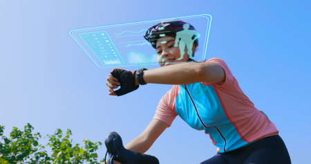 asian female biker looking at smart watch for fitness tracking while riding road bike