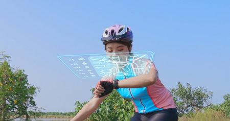 Athlete female biker using activity tracker gps fitness watch on biking workout