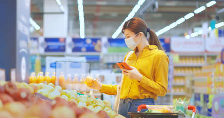 asian young businesswoman wearing face mask is shopping for fresh organic fruits and check shopping list with smart phone at supermarket during virus epidemic outbreak