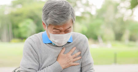 close up of asian elderly man suffering from bad pain in his chest heart attack at park