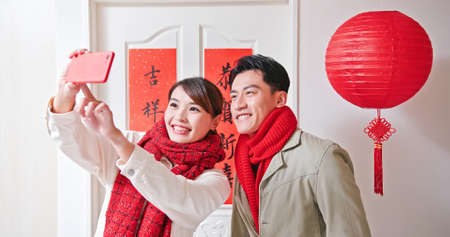 Loving asian young couple making a selfie in front of the door with spring festival couplets