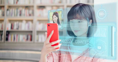 young woman use smart phone unlocking with biometric facial identification indoor