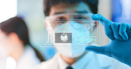 asian male scientist analyzing structure of DNA on a tablet in a modern laboratory environment-using display technology to examine neurons