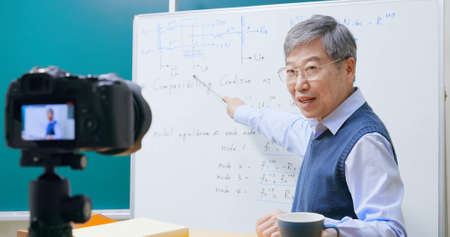 Asian mature male professor having online class is using digital video camera record during teaching math course at graduate school to prevent coronavirus infection Zdjęcie Seryjne