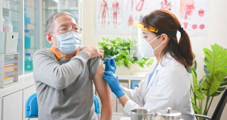 asian female doctor wearing gloves and isolation mask is making a vaccination in the shoulder of senior male patient at hospital