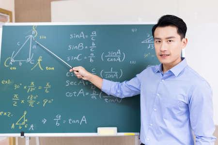 asian senior high school male teacher teach math online through webcam in classroom Standard-Bild