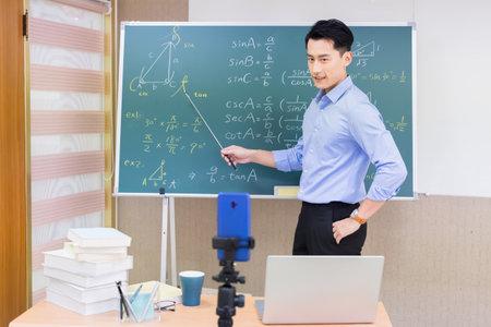 asian senior high school male teacher teach math online through mobile phone in classroom
