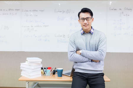 asian young male teacher smiles at you with cross arm in classroom