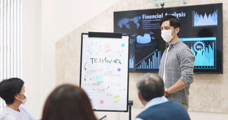 Asian business team wear facial mask in a meeting and a young male leader emphasize the importance of teamwork