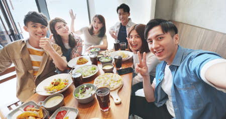 high angle shot of asian young six friends taking selfie in restaurant happily