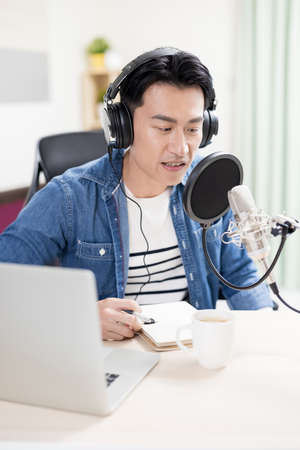 asian man with headphones and microphone recording podcast at studio with laptop Imagens