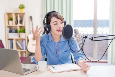 asian woman with headphones and microphone recording podcast at studio