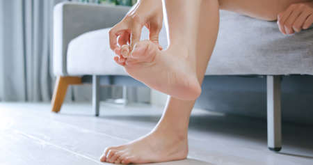 asian woman scratch her athlete foot while sitting on sofa